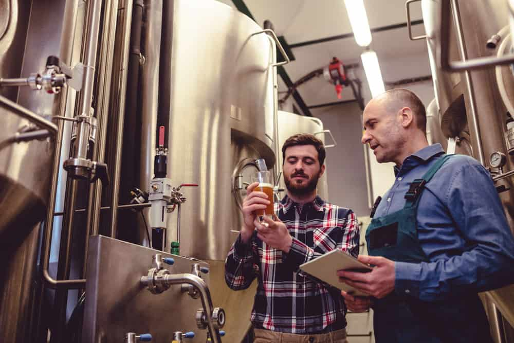 Owner inspecting beer with worker at brewery